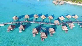 Het hotel van de bungalowbrug in het overweldigen van turkooise Vreedzame oceaan op Bora Bora-eiland Frans Polynesia 4k lucht tro stock videobeelden