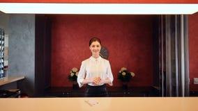 Het hotelgast van de receptionnistgroet, die ruimtesleutel geven 4K stock videobeelden