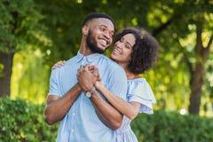Het houden van van Afrikaans-Amerikaans paar die in de zomerpark koesteren royalty-vrije stock fotografie