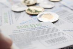 Het houden van Canadese besparingscoupons met geld, stock fotografie