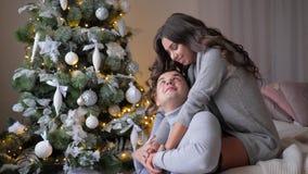 Het houden van de emoties, jonge vrouw zitten op laag en dichtbij het koesteren van echtgenoot aan spar op vooravond van Kerstmis stock videobeelden