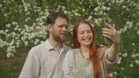 Het houden van de paarlevensstijl gebruikt videopraatje, genietend van online communicatie met vrienden en zijnd in een mooi Park stock footage