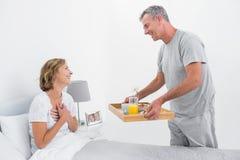 Het houden van echtgenoot van brengend ontbijt in bed aan vrouw Stock Foto's
