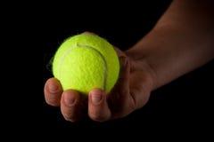 Het houden van een Bal van het Tennis op Zwarte Stock Foto