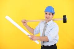 Het houden van een blauwdruk en een houten hamer Stock Foto's