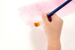 Het houden van een borstel aan verf Stock Fotografie