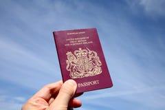 Het houden van een Brits paspoort. Stock Foto's