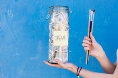 Het houden van een flessenhoogtepunt van geldbesparingen voor droom Royalty-vrije Stock Fotografie