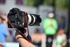 Het houden van een fotocamera stock afbeelding