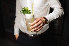 Het houden van een glas van mojitococktail stock fotografie