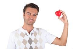 Het houden van een hart-vormig voorwerp Stock Afbeelding