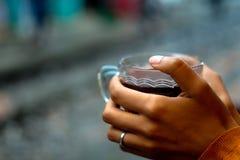 Het houden van een kop van koffie door sporentrui stock foto's