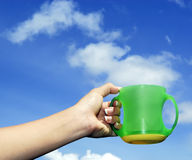 Het houden van een kop tegen zonnige blauwe hemel met wolk Royalty-vrije Stock Foto's
