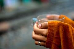 Het houden van een kop thee door sporentrui die handen behandelen door de helft royalty-vrije stock foto's