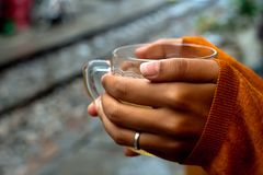 Het houden van een kop thee door sporentrui die handen behandelen door een derde royalty-vrije stock afbeelding