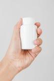 Het houden van een witte fles van pillen Royalty-vrije Stock Afbeelding