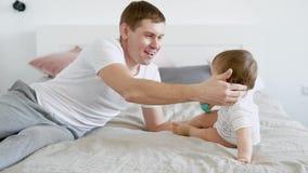Het houden van van gevende vader speelt met zijn klein kind en het strijken van zijn hoofd in slaapkamer in vakantie stock video