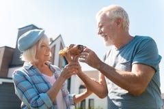 Het houden van van glimlachende echtgenoot die zijn richtend vrouwencroissant met chocolade geven royalty-vrije stock afbeelding