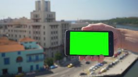 Het houden van het Groene Scherm Smartphone boven Havana Cuba stock footage