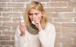 Het houden van het medicijn in haar neus Het lijden aan astma of allergisch Rhinitis Zieke vrouw met neusdalingen Mooi meisje stock foto's