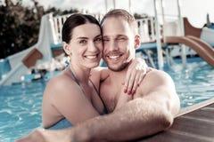 Het houden van van millennial paar die in zwembad omhelzen royalty-vrije stock afbeelding