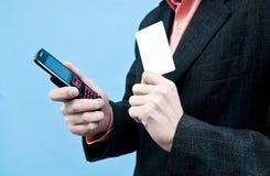 Het houden van mobiele en witte kaart Stock Afbeelding