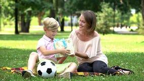 Het houden van moeder aanwezige geven aan zoon op verjaardag, belichaming van kinddroom royalty-vrije stock fotografie