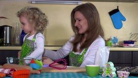 Het houden van moeder van gezette het meisjesschort van de peuterdochter in keuken stock footage