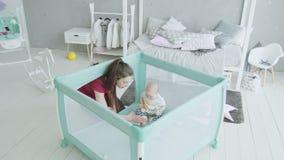 Het houden van moeder het spelen met zuigelingsmeisje in box stock videobeelden