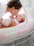 Het houden van moeder van kussende baby in bed Stock Fotografie