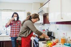 Het houden van Mum-Bedrijf terwijl zij Voedsel voorbereidt stock fotografie