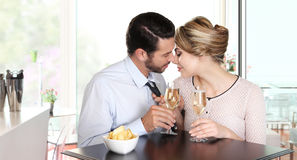 Het houden van paar het kussen zitting bij een lijst met wijn royalty-vrije stock fotografie