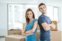 Het houden van paar het stellen in hun nieuw huis Stock Foto's