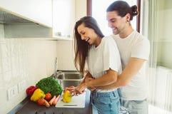 Het houden van paar het koken in de keuken stock foto's