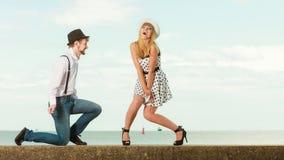Het houden van paar van retro stijl die op overzeese kust dateren Stock Foto