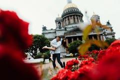 Het houden van paaromhelzingen tegen een achtergrond van rode bloemen en uitstekende architectuur Stock Foto