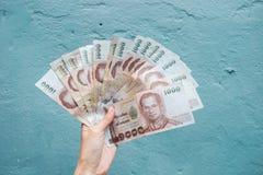 Het houden van Thais bankbiljet 1000 Baht op blauwe achtergrond Royalty-vrije Stock Afbeeldingen