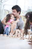 Het houden van vader het kussen dochterbouwstenen op vloer Royalty-vrije Stock Foto's