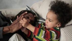 Het houden van vader het spelen met zijn zoon op de bank stock videobeelden
