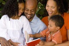 Het houden van van Afrikaanse Amerikaanse ouders die met hun jonge geitjes lezen Stock Afbeeldingen