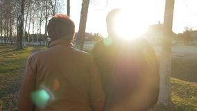 Het houden van van bejaard paar die in het park bij zonsondergang lopen Dichtbij er is een weg Een vrouw in een bruin leerjasje D stock footage