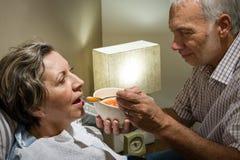 Het houden van van teruggetrokken echtgenoot die zijn zieke vrouw voeden Stock Afbeeldingen
