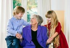 Het houden van van weinig jongen en meisje met hun grootmoeder Stock Afbeelding