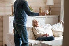 Het houden van van verouderde echtgenoot brengende thee aan glimlachende vrouw stock foto's