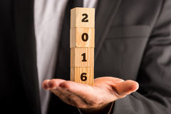 Het houden van vier gestapelde houten kubussen met het teken van 2016 Stock Afbeeldingen