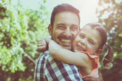 Het houden van zijn dochter in zijn wapens en het bekijken camera Stock Foto's