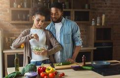 Het houden van van zwart paar die diner in keuken voorbereiden stock afbeeldingen