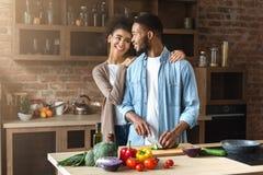 Het houden van van zwart paar die salade in zolderkeuken voorbereiden stock fotografie