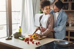 Het houden van van zwarte echtgenoot die vrouw koesteren terwijl het koken stock foto