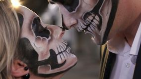 Het houdende van paar die van Halloween met schedelmake-up elkaar bekijken stock videobeelden